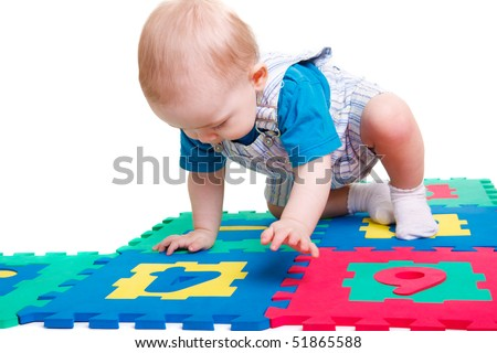 Baby boy sitting on the numeric puzzle mat
