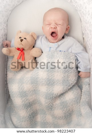 baby boy  sleeping in a basinet  with a stuffed teddy bear
