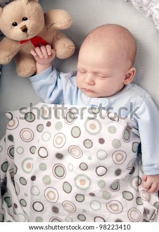 baby boy  sleeping in a basinet  with a stuffed teddy bear