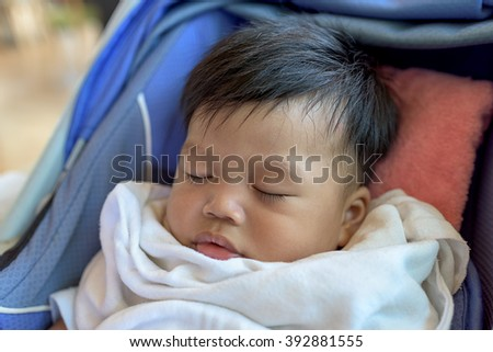 baby boy sleeping in child car seat. #392881555