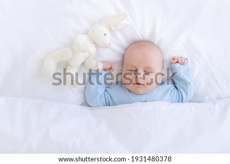 baby boy sleeping on the bed lying on his back with a stuffed toy hares in blue pajamas hands up, healthy newborn sleep