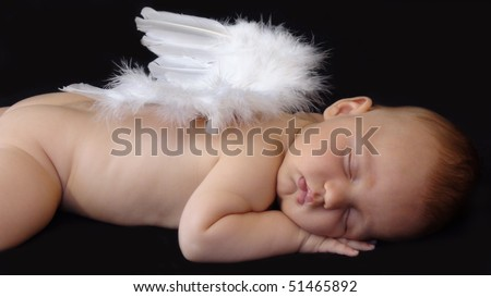 Baby boy sleeping with angel wings on his back