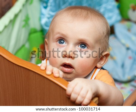 Baby boy standing in cot (crib) and looks up