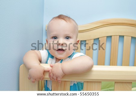 Baby boy standing in crib, smiling