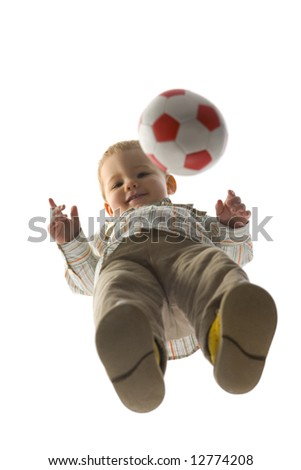 Baby boy standing with ball and looking at camera. Isolated on white background. Unusual angle view - directly below.