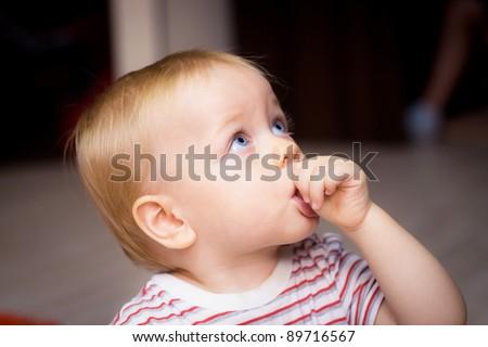 Baby boy sucking his thumb at home