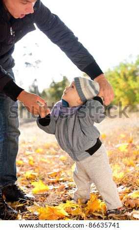 baby boy taking first steps with father help in autumn park