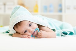baby boy using teether under towel after bathing at home