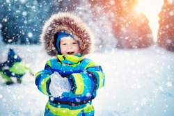 Baby boy walking at snowfall. Child in winter clothes playing with snow