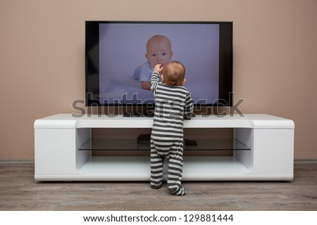 baby boy watching TV at home