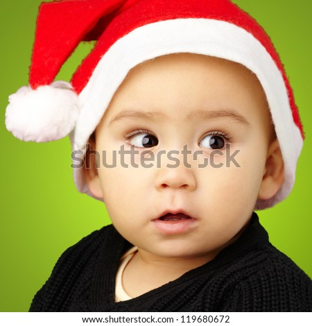Baby Boy Wearing Santa Hat Holding Christmas Ornaments against a green background