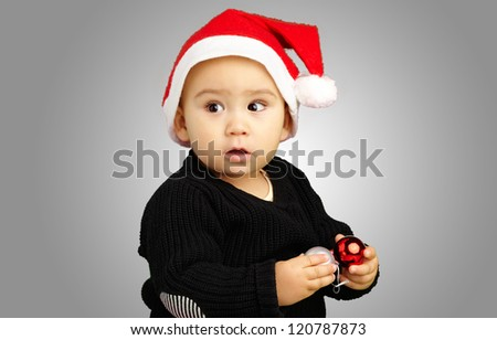 Baby Boy Wearing Santa Hat Holding Christmas Ornaments against a grey background