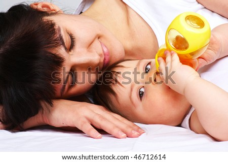 baby boy with bottle laying with mother in bed