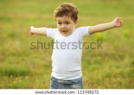 baby boy with brown hair having fun in the park, doing morning exercise. outdoor shot