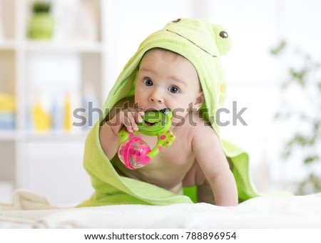 Baby boy with green towel after the bath biting toy. #788896954