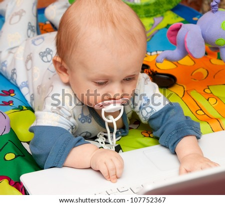 Baby boy with interest works with (computer) laptop