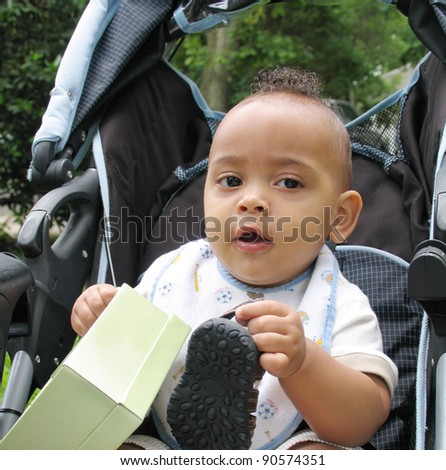 Baby Boy with Mohawk Hairstyle holding shoe and box