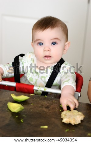 Baby boy with ricecake and avocado to eat - stock photo