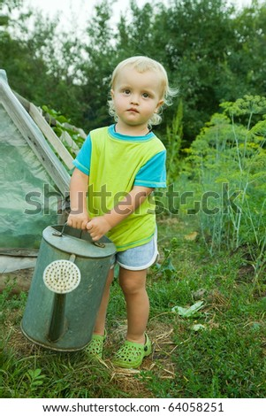 baby boy with watering pot in summer garden