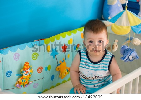 Baby boy ( 1 year old ) sitting in baby bed at children's room, looking up.