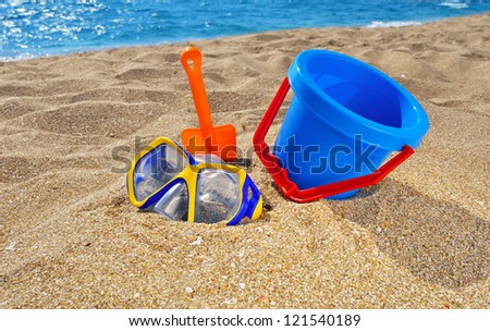 Baby bucket, shovel  and diving mask on the beach against the azure sea