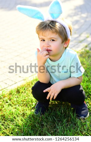 Baby bunny. Cute boy with bunny ears crouched in the park. The child sits on the green grass and plays like rabbit. Funny baby boy