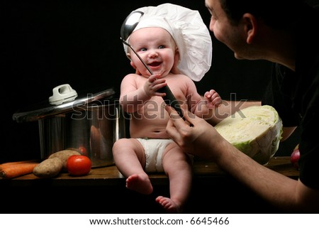 Baby chef and father play together
