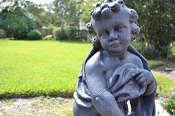 Baby cherub garden park sculpture with greenery in background