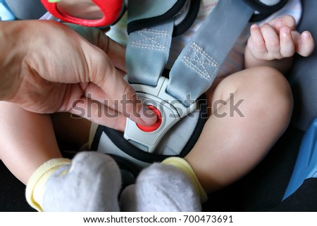 baby child sitting in car seat with safety belt locked protection