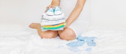 Baby clothes and a pregnant woman. Selective focus. people.