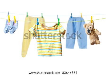 Baby clothes and a tearful teddy bear drying on a rope isolated on white background