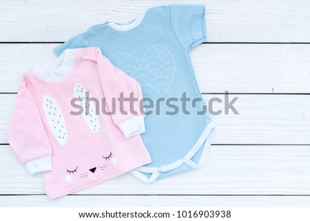 Baby clothes concept. Blue bodysuit for boy and pink shirt for girl on white wooden background top view copyspace