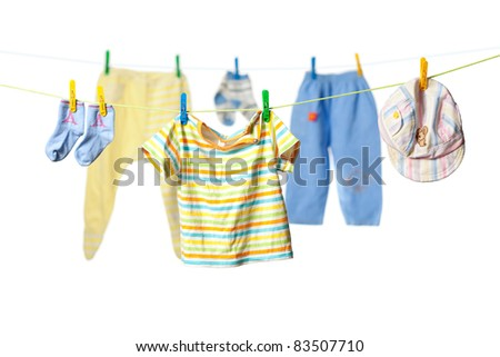 Baby clothes drying on a rope isolated on white background