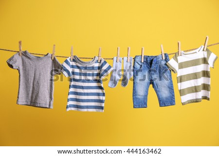 Baby clothes hanging on rope on yellow background #444163462