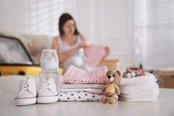 Baby clothes with accessories on white table and pregnant woman packing suitcase for maternity hospital indoors