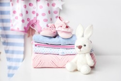 Baby clothes with booties and toy on table in room