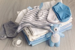 baby clothes with diapers are stacked with a pacifier and a toy bear