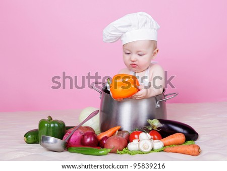 Baby cook with pepper in hands