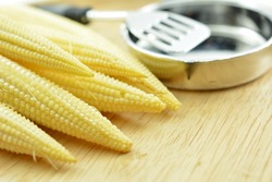 Baby corn for cooking on wood board, Baby corn, young corn, or cornlettes, is a cereal grain taken from corn (maize) harvested early while the stalks are very small and immature.