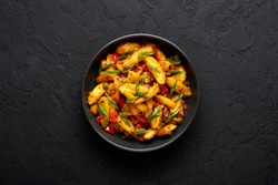 Baby Corn Manchurian dry looks like Schezwan Baby Corn in black bowl at dark slate background. Baby Corn Manchurian - is indo chinese cuisine dish with deep fried corn, bell peppers, sauce and onion.