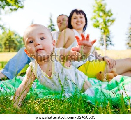 Baby crawling and his parents behind, focus on baby - stock photo