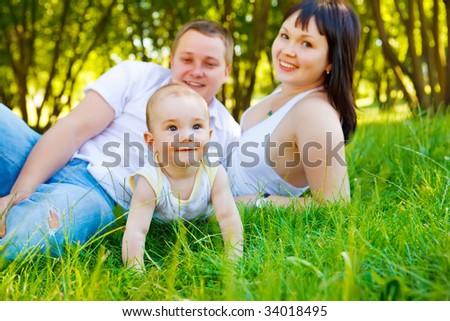 Baby crawling, his happy parents look at him