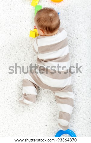 Baby crawling on the floor - top view