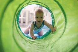 Baby crawling through play tunnel
