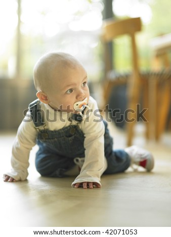 Baby crawling with pacifier in mouth. Vertically framed shot.