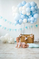 baby crawls on the floor on background of a wicker basket with balloons with a place for text