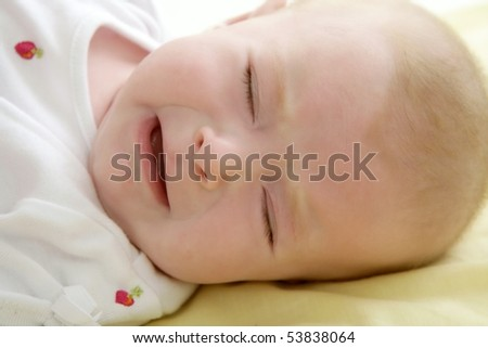 baby crying sad laying on the yellow bed