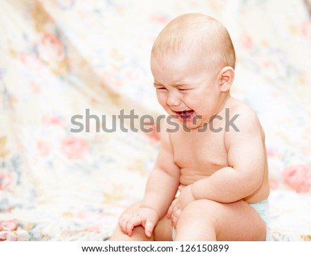 Baby crying sitting  on the floor