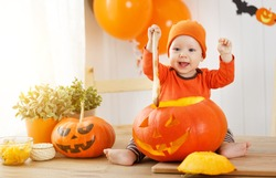 baby cut a pumpkin for Halloween in the kitchen at home