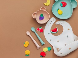 baby dishware on brown background, Flat lay composition with kids accessories, first food for baby, first feeding concept
